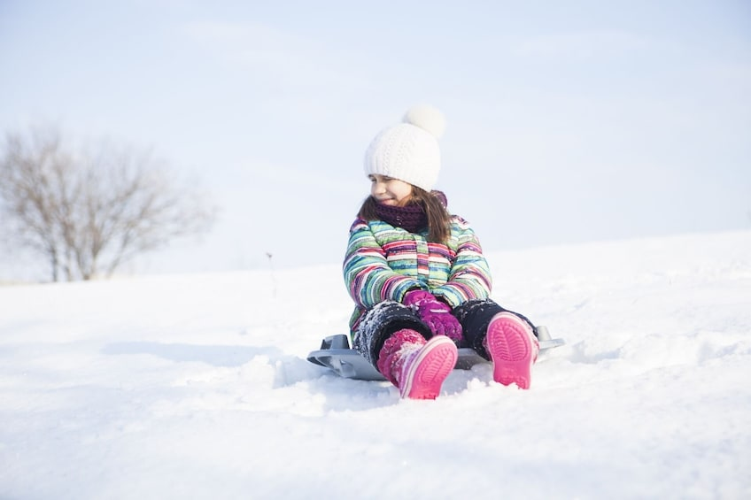 Show item 1 of 5. Little girl sits on round sled in snow at Yeti Snow Park