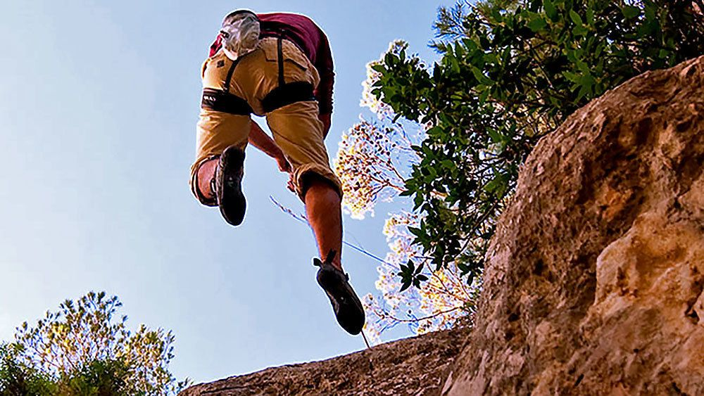 Man repelling from the edge of a cliff in Mallorca
