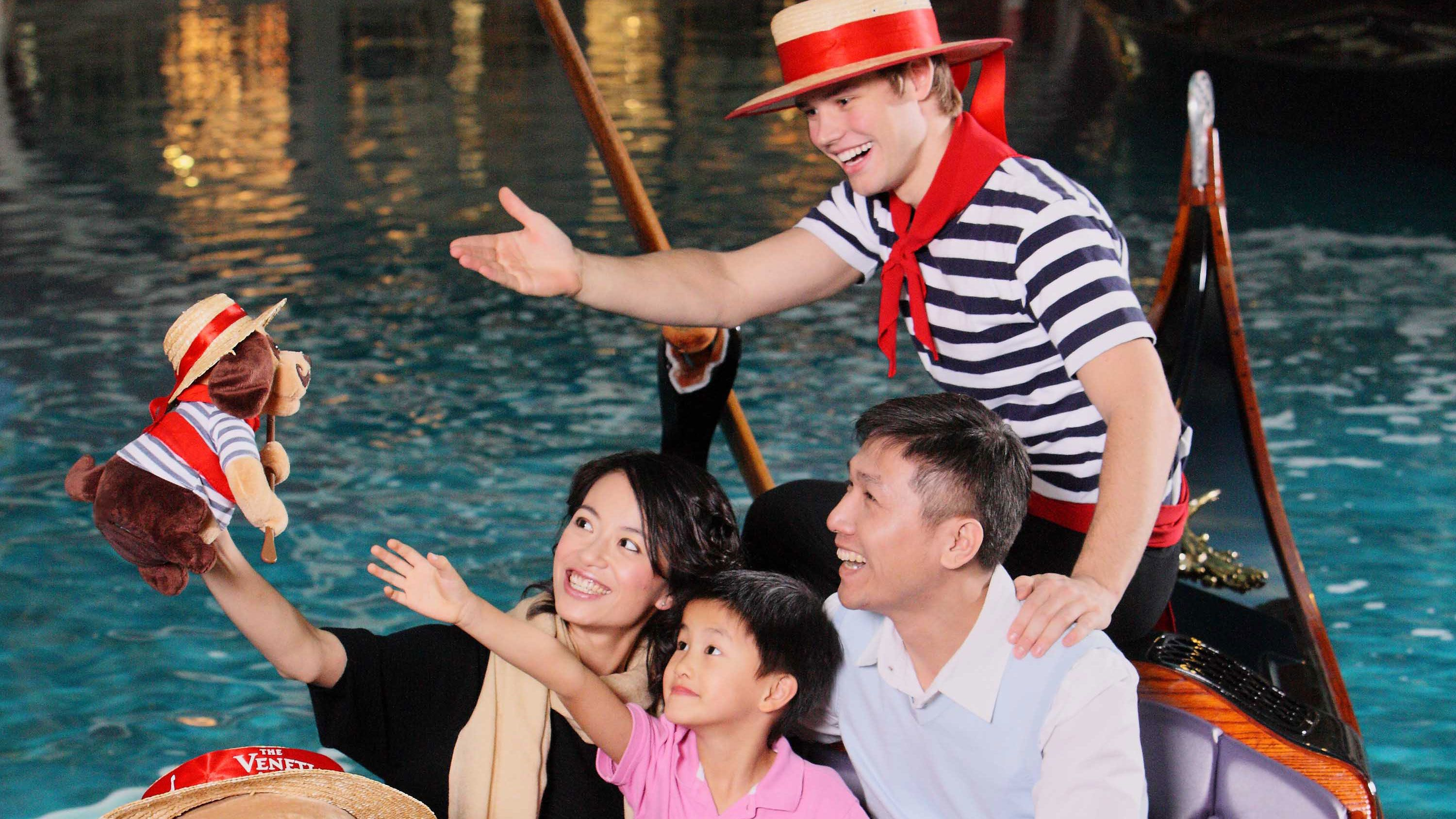 Happy Family of three being entertained by male Gondolier