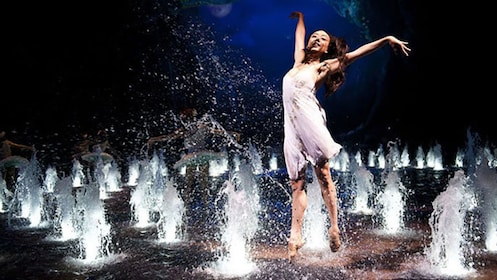 woman dancing amidst many water fountains.