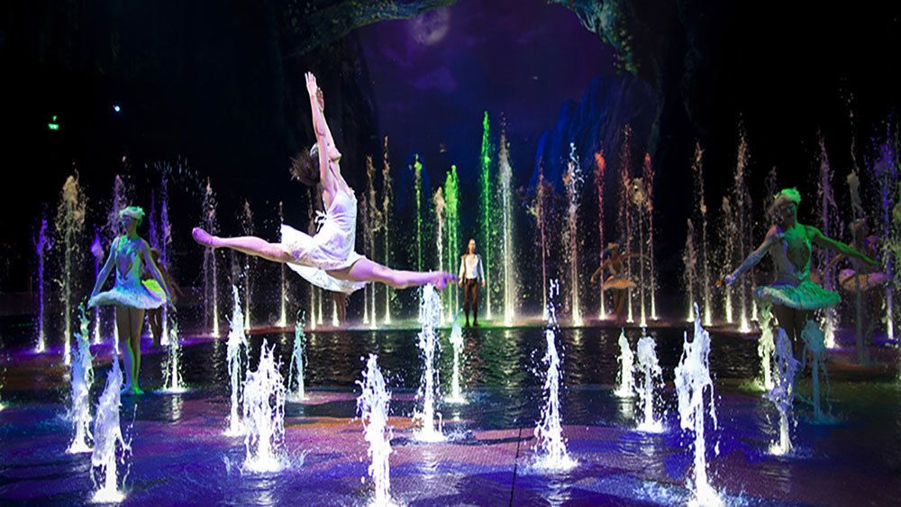 women dancing and leaping amidst many water fountains.