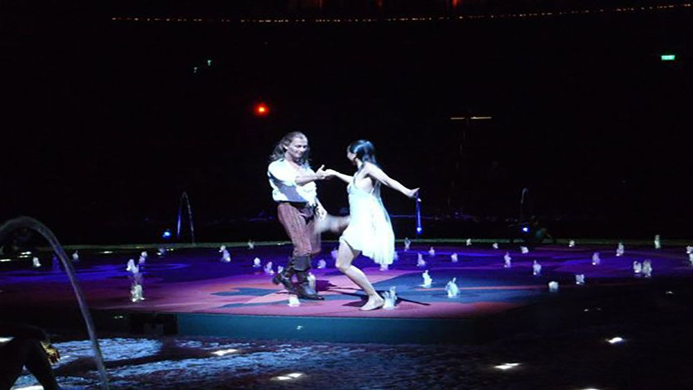 svelte man and woman dancing amidst a circle of water fountains.