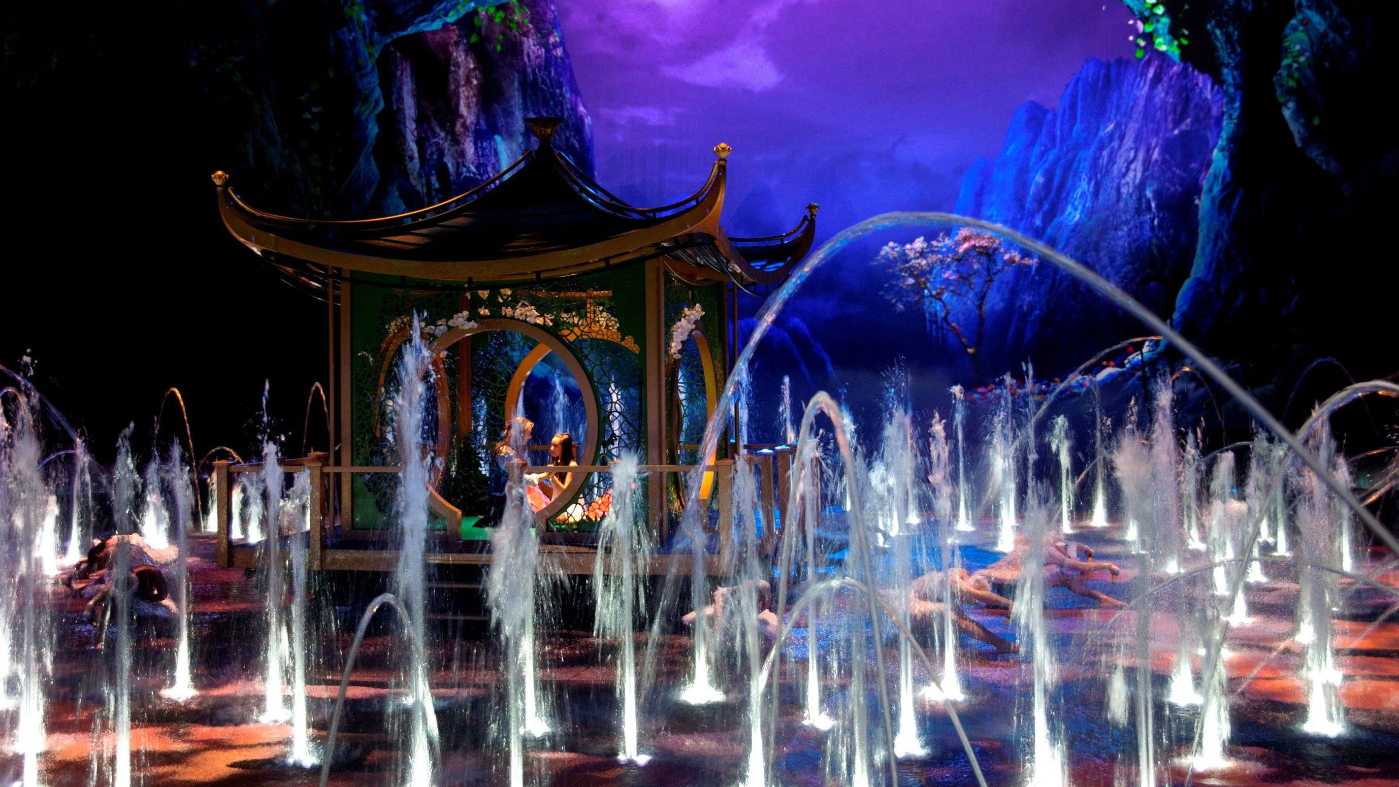 many water fountains spouting water surrounding performers