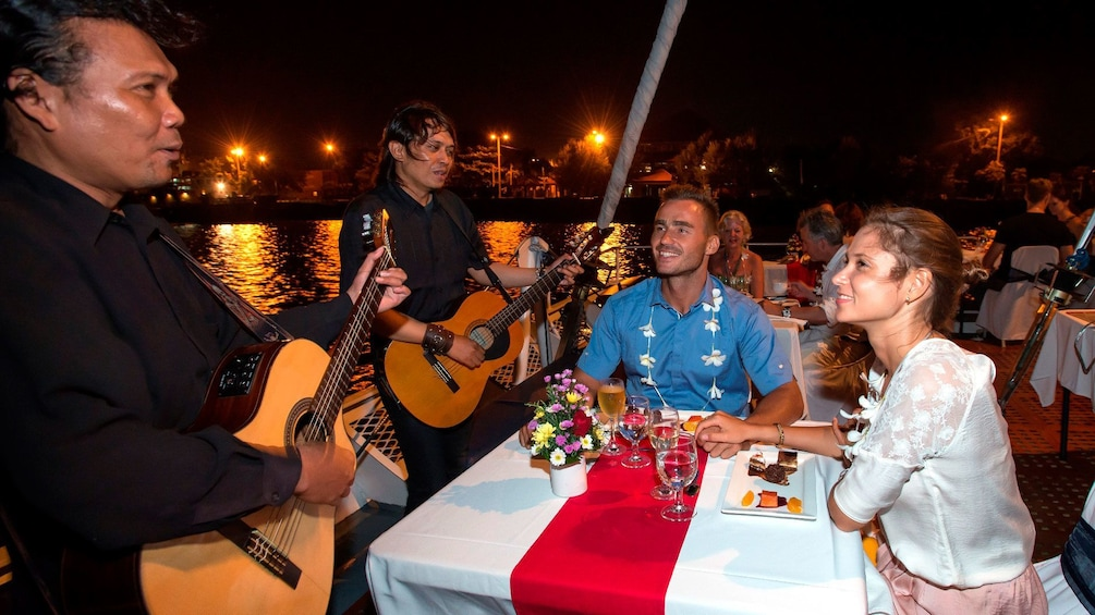 Tampilkan item 4 dari 5. Musicians playing their guitar for a couple on a night cruise in Bali Hai