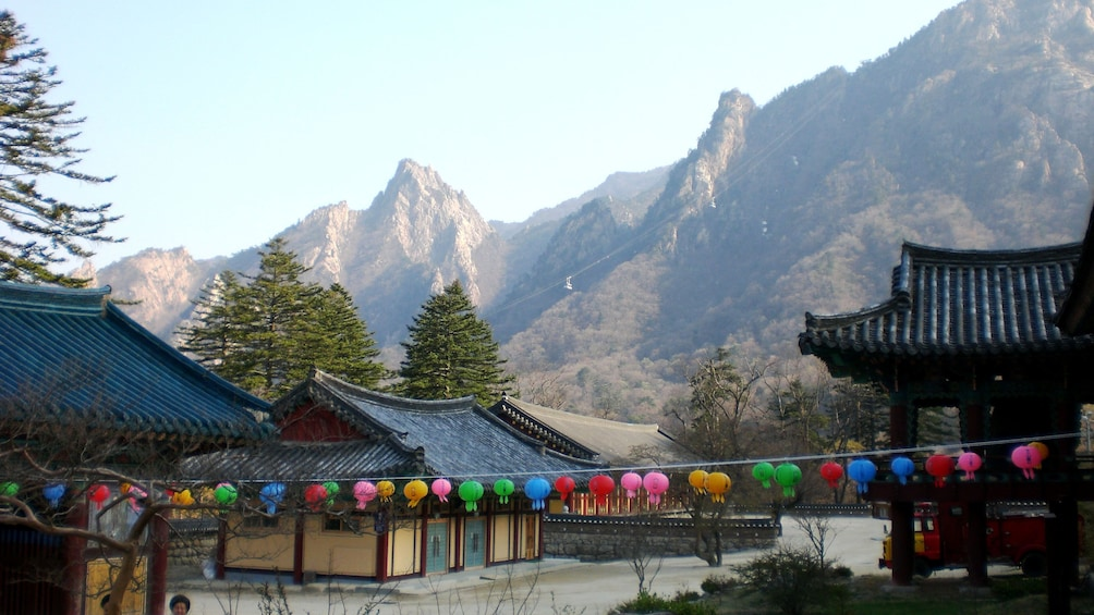 Show item 4 of 5. Colorful lanterns strung across traditional style buildings with mountains in the background in Seoul