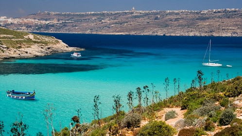 Boats in the clear blue water off the coast of Comino Island