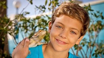 Indlæs billede 10 af 10. Young boy with iguana on his shoulder at Marine Park in Malta