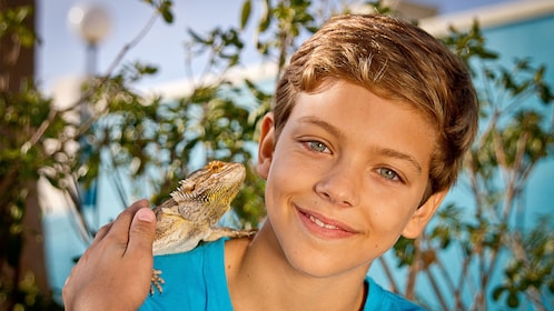 Young boy with iguana on his shoulder at Marine Park in Malta
