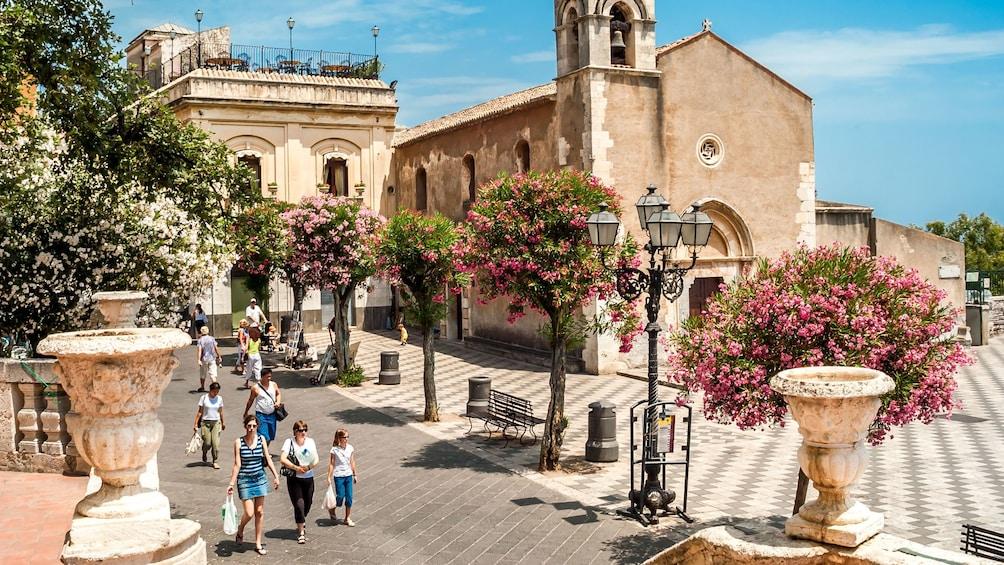 Tourists walking through the city center in Taormina