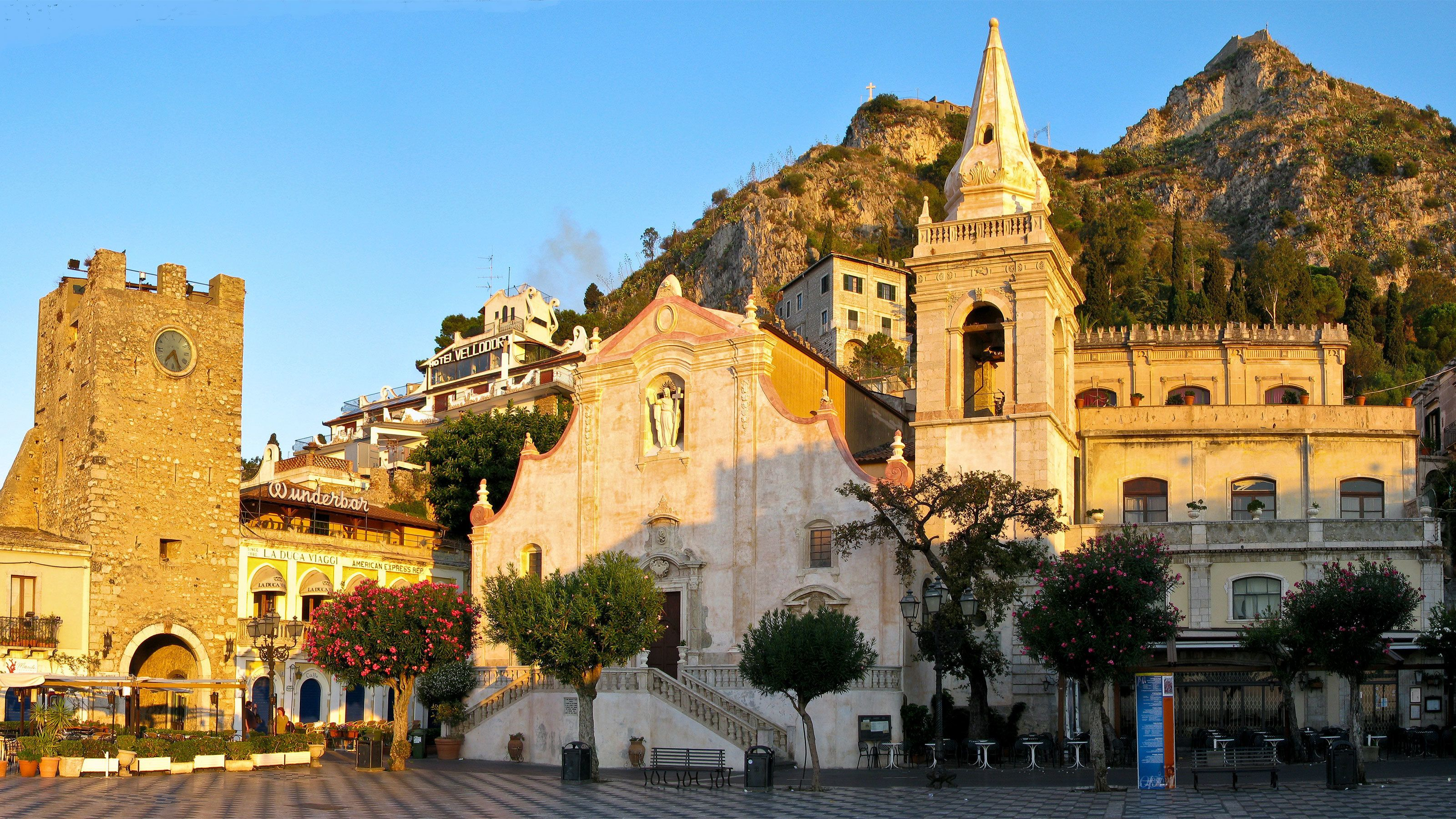 Historical buildings in the city center with mountains in the background in Taormina