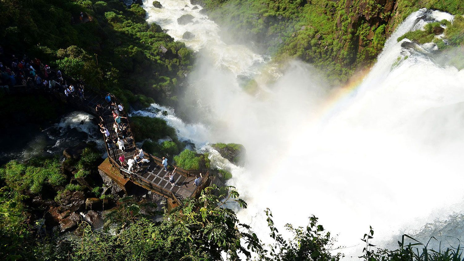 Trail with people at the base of a waterfall in Iguazu.