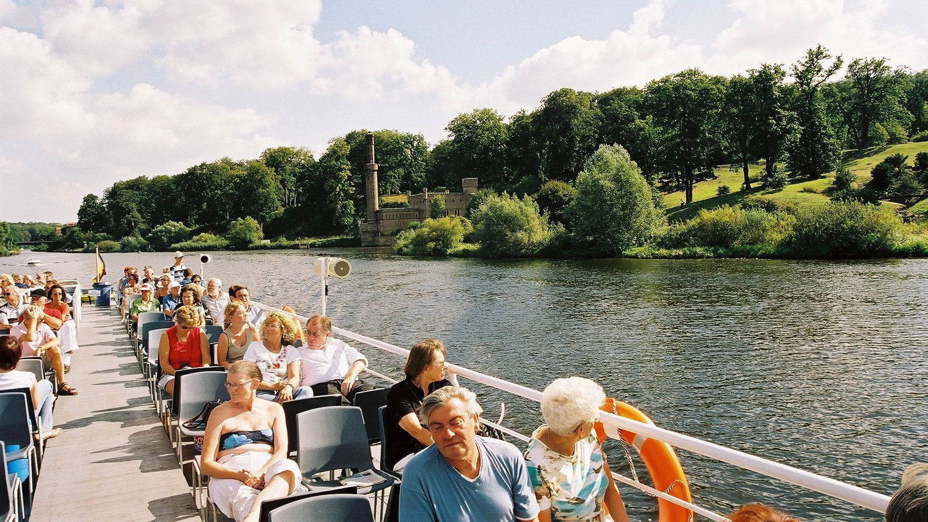 Cruising passengers enjoy the scenery on tour boat in Berlin.