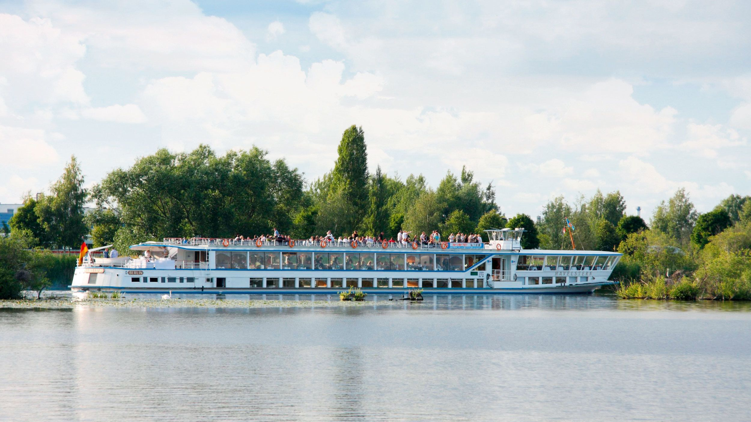 Tour boat with passengers on lake in Berlin.