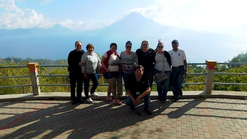 Group takes photo in front of mountain range in Santiago village
