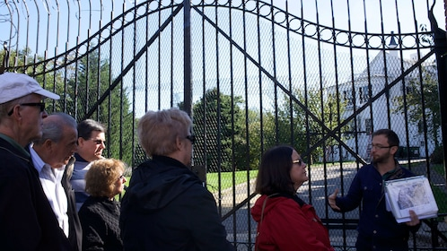 Tour guide talks to group outside of gate in Brooklyn Navy Yard