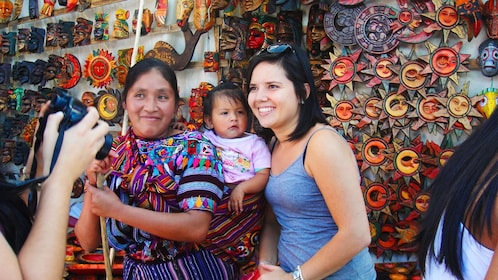 Tourist takes photo with local at Chichicastenango market in Guatemala