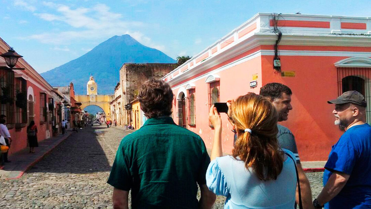 People taking pictures down street of Antigua