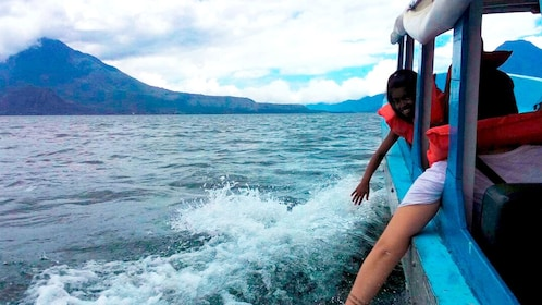 People hanging arms out of boat to touch the waters of Lake Atitlan