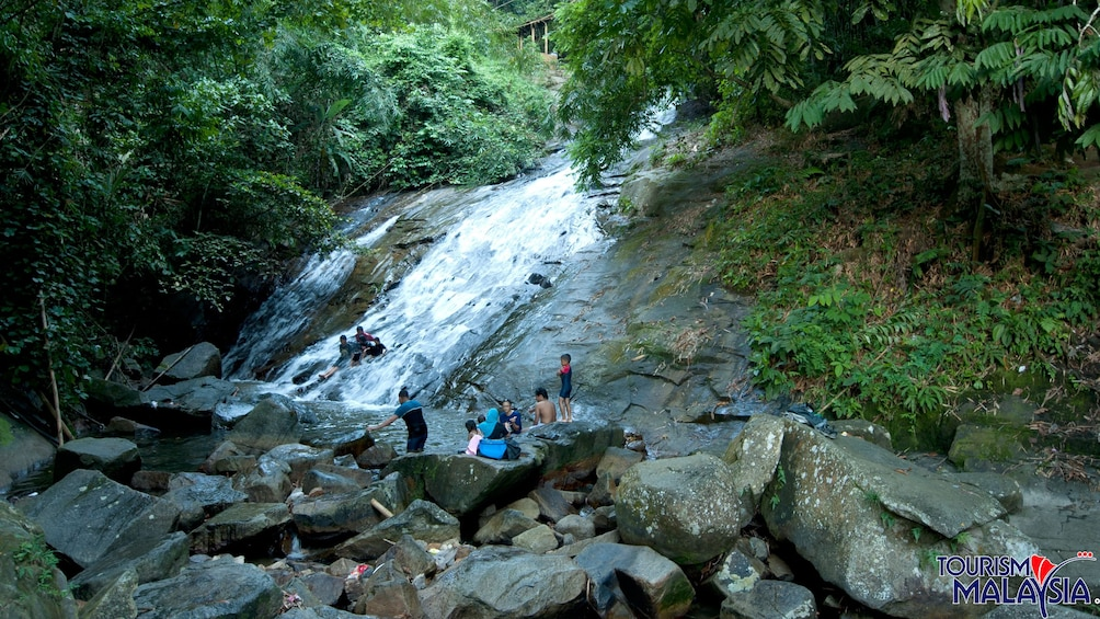 Show item 1 of 5. Group sliding down a rock waterfall at Templer's Park in Malaysia