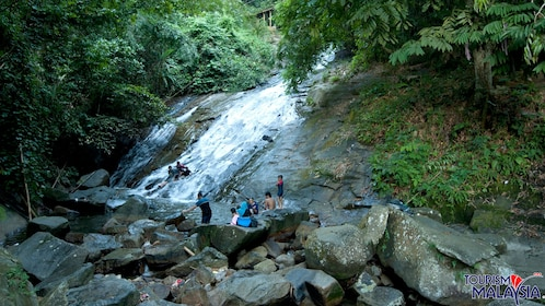 Group sliding down a rock waterfall at Templer's Park in Malaysia