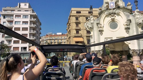 Passengers on the upper level of a hop-on hop-off bus tour in San Sebastian