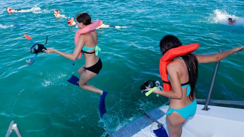 two girls in snorkeling gear jump into water from deck of sailboat in Los Cabos