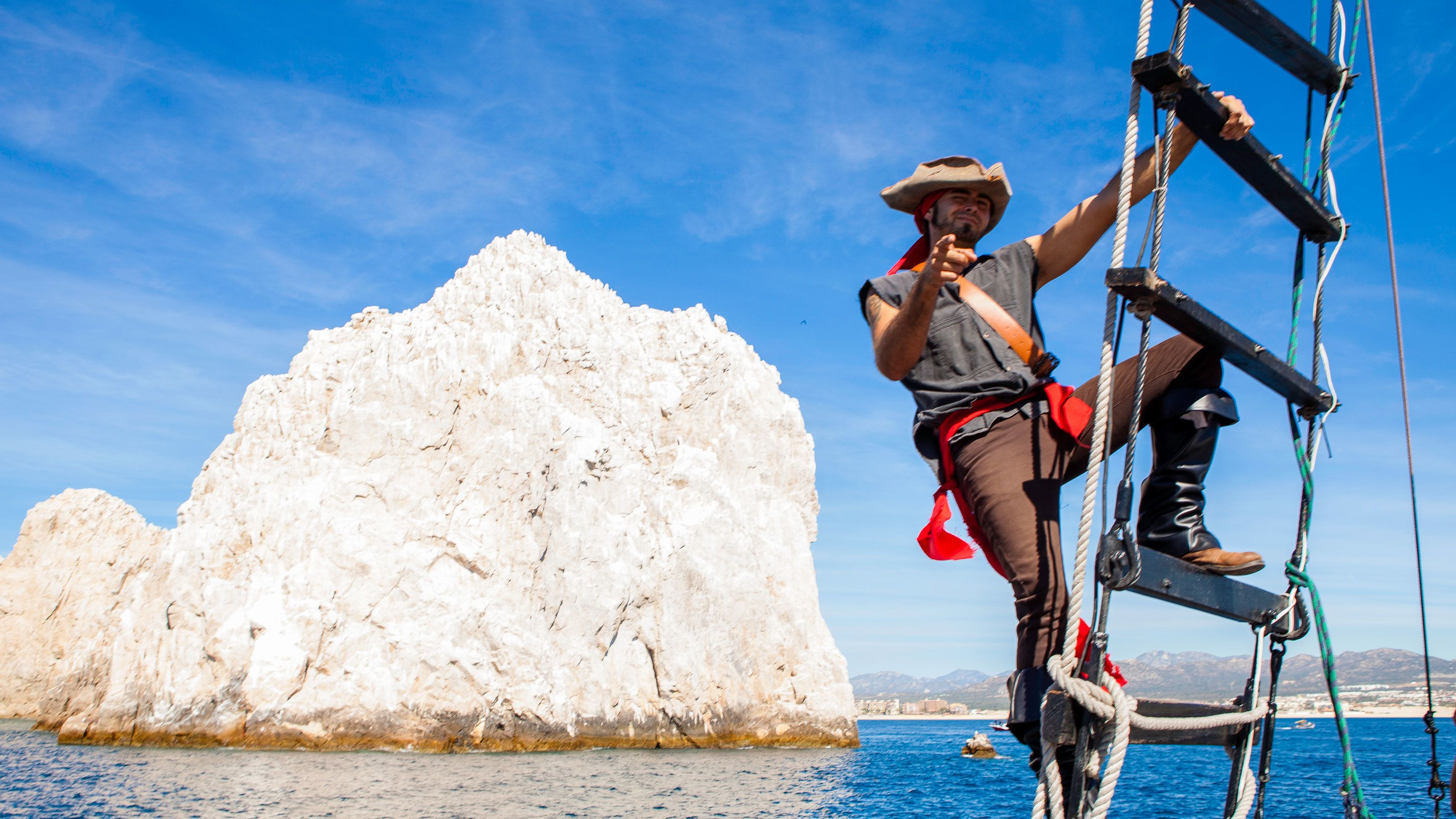 man in pirate costume on ladder in front of sea stack in Los Cabos