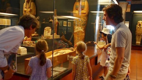 A family looking at mummies in a museum in Rome