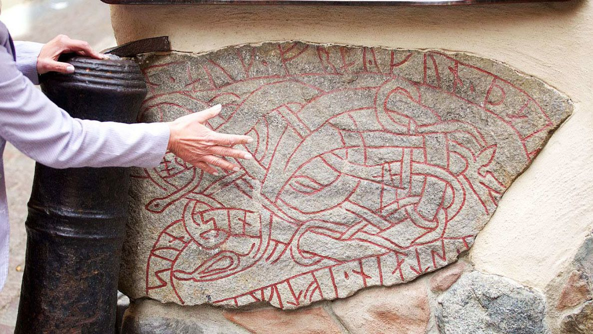 Tour guide describes the inscription on a Viking Rune Stone in Old Town Stockholm