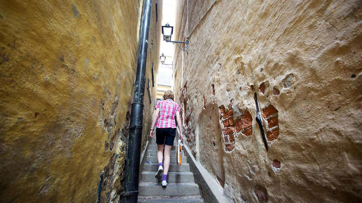 Woman walking up narrow staircase between buildings in Stockholm