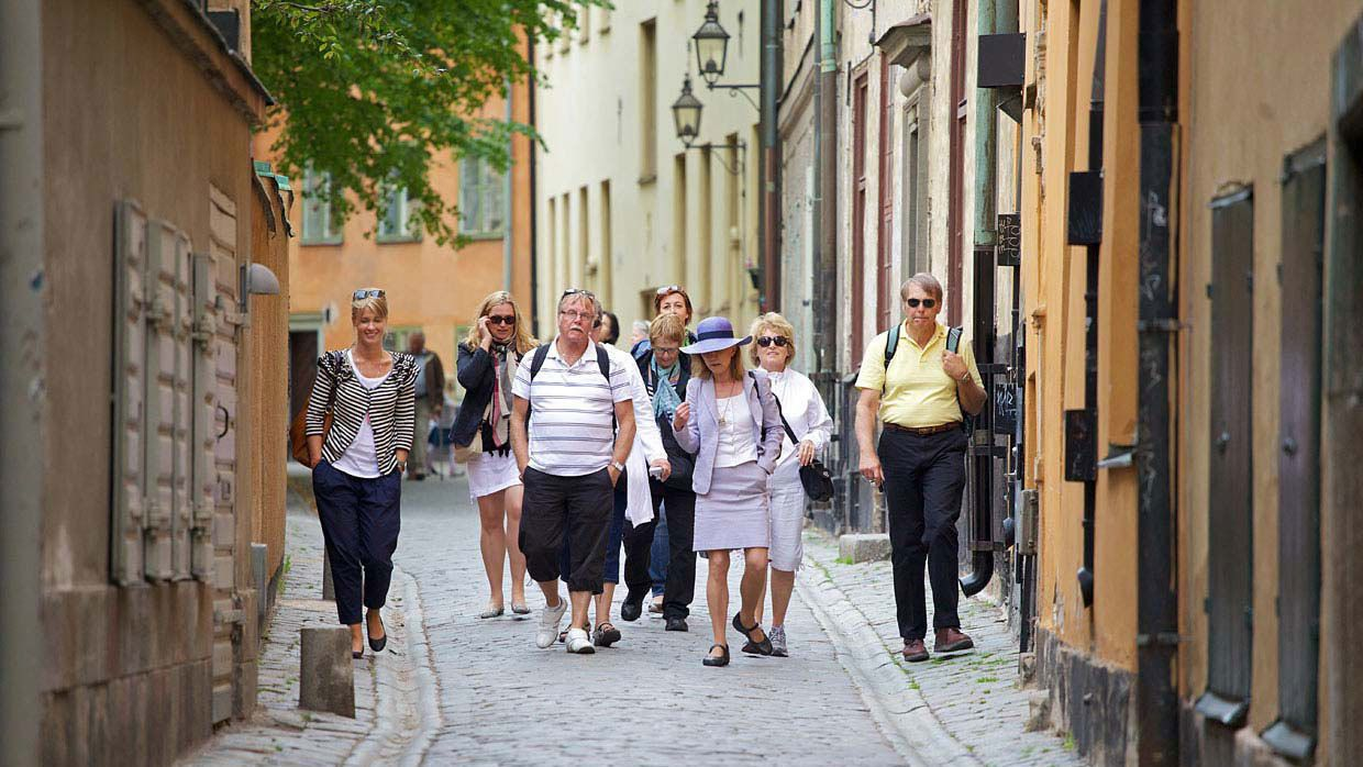 Tour guide and group walking through Old Town in Stockholm