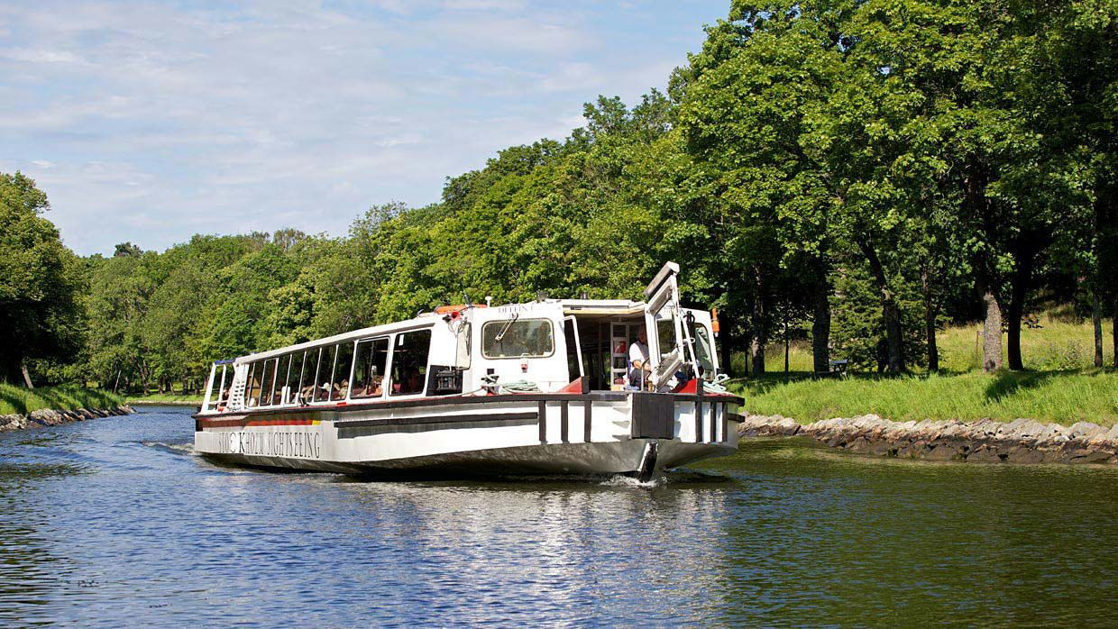 Sightseeing boat on a canal with trees on either side in Stockholm