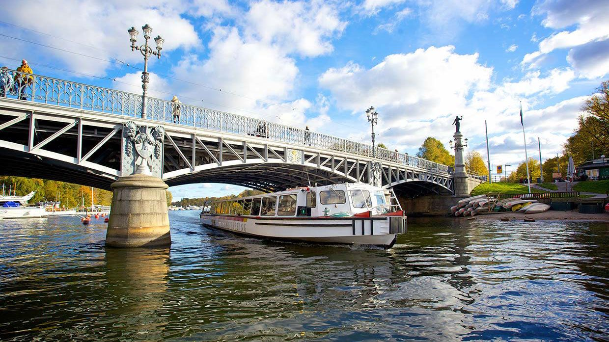 Sightseeing boat passing under a bridge in Stockholm