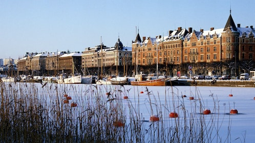 Snow-covered water and boats with the city of Stockholm in the background