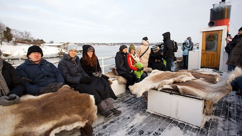 Sightseeing cruise passengers with fur blankets in Stockholm