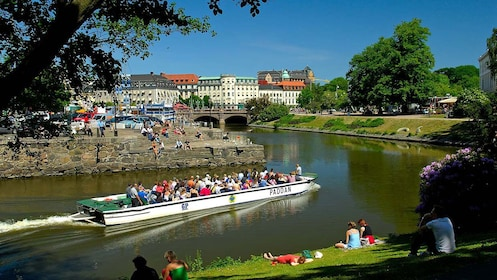 Open-top boat with passengers passing through a canal in Gothenburg