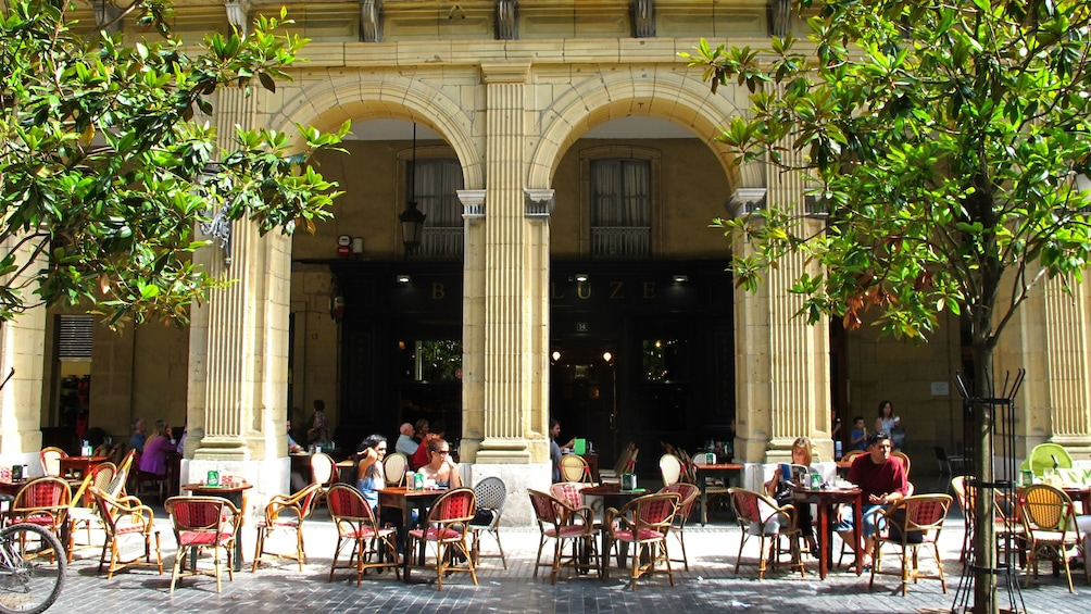 People sitting outside at tables for a cafe in San Sebastián