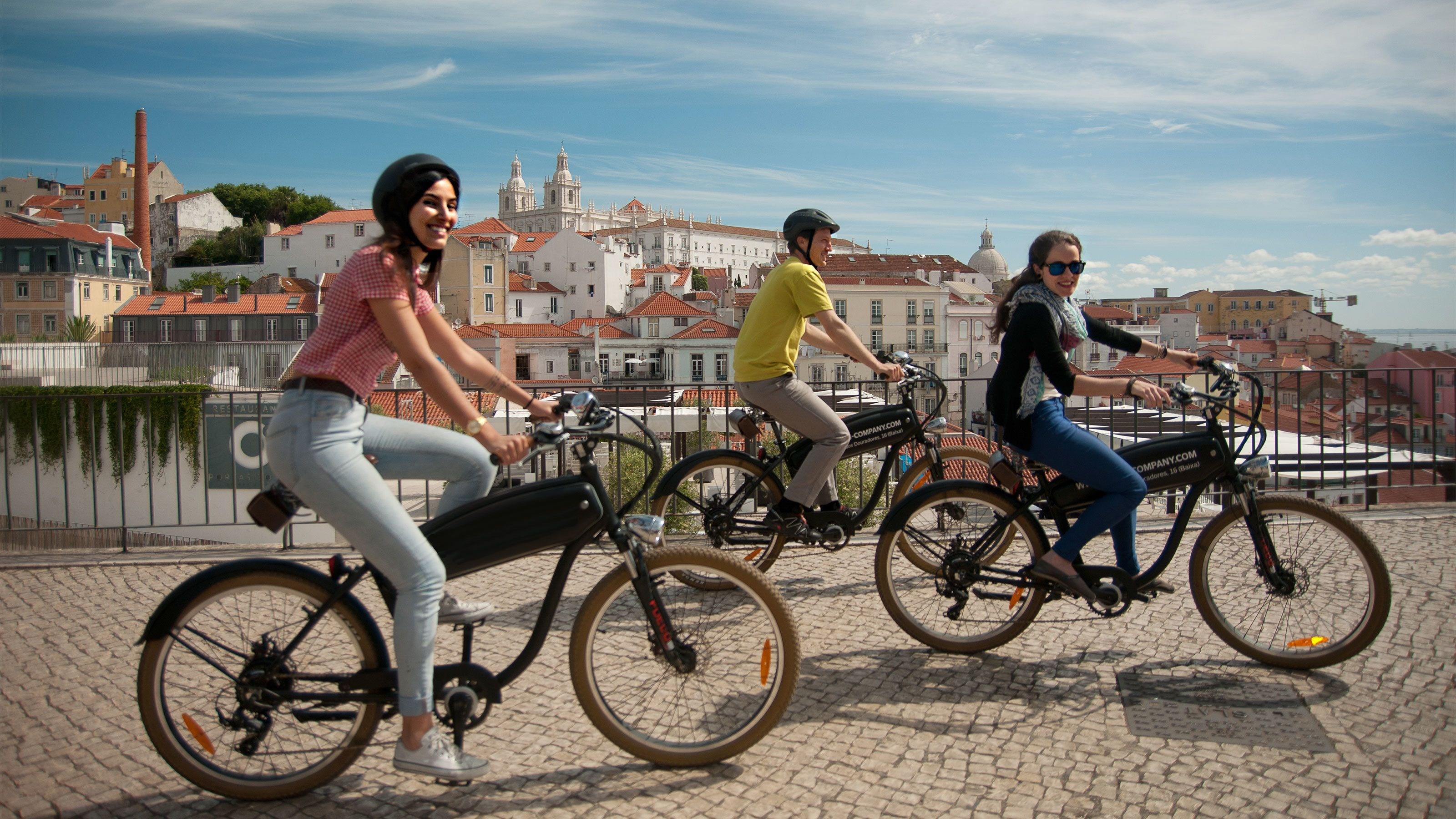 Bicycling group on a cobblestone street in Lisbon