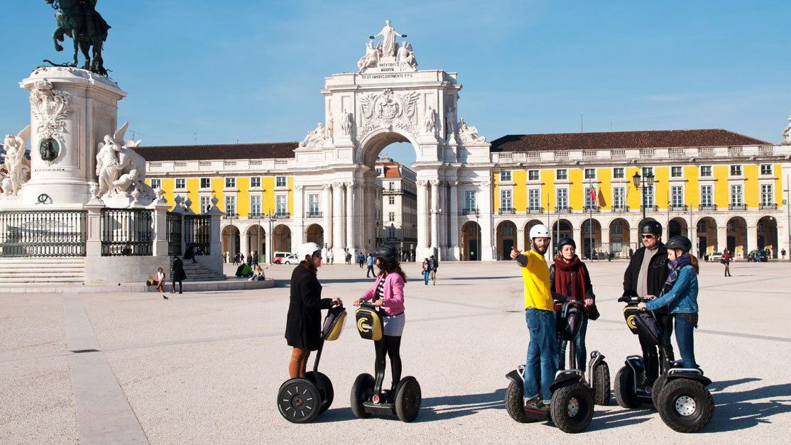 Segway group near the statue and arch in Palace Square in Lisbon