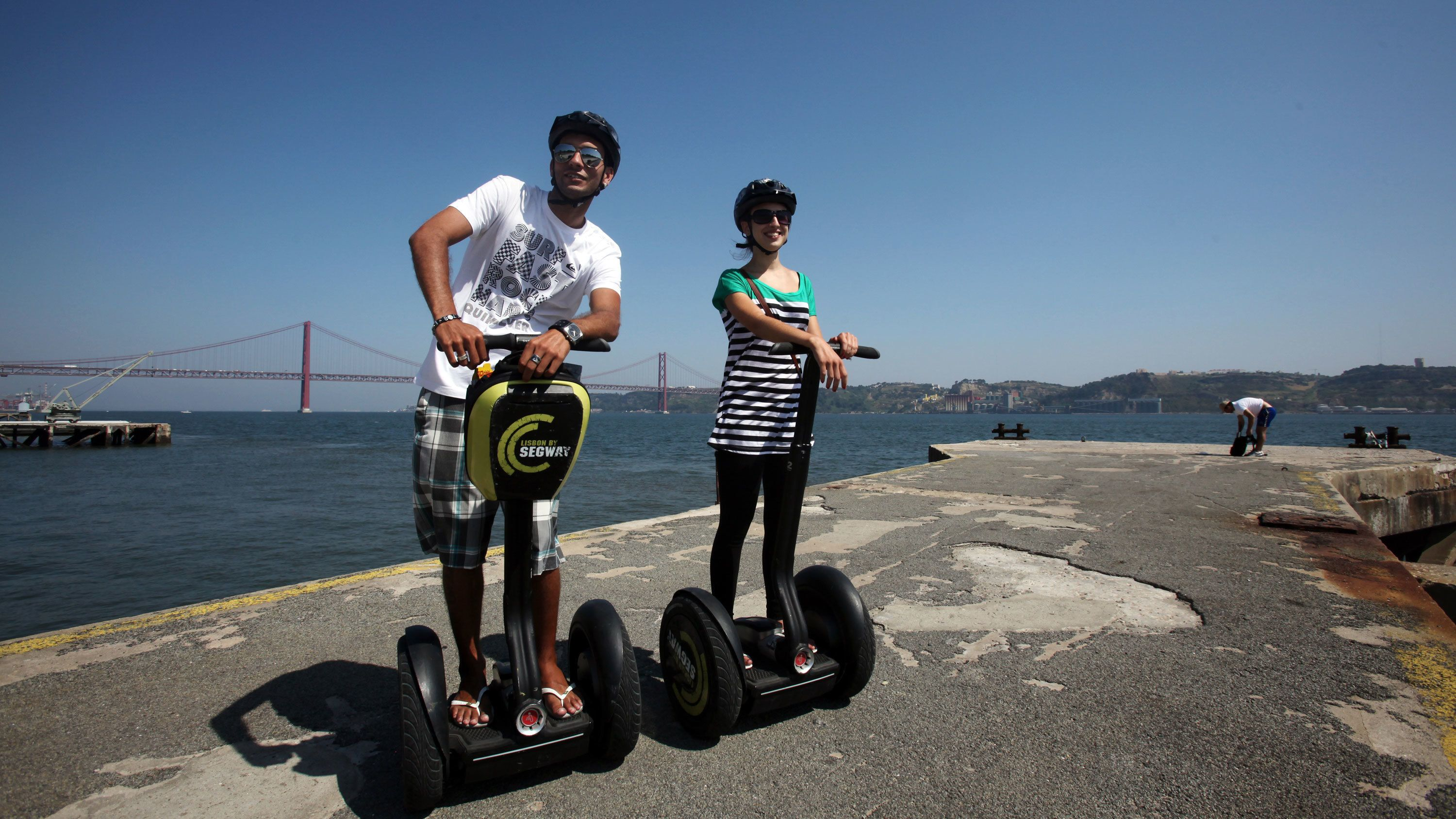 Segway couple on a pier with bridge in the background in Lisbon