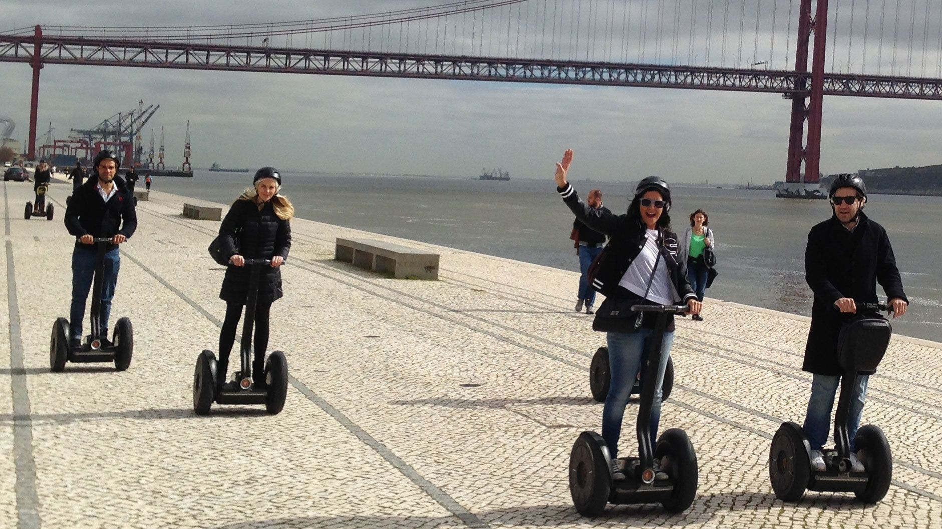 Segway group on path along the coast with bridge in the background in Lisbon