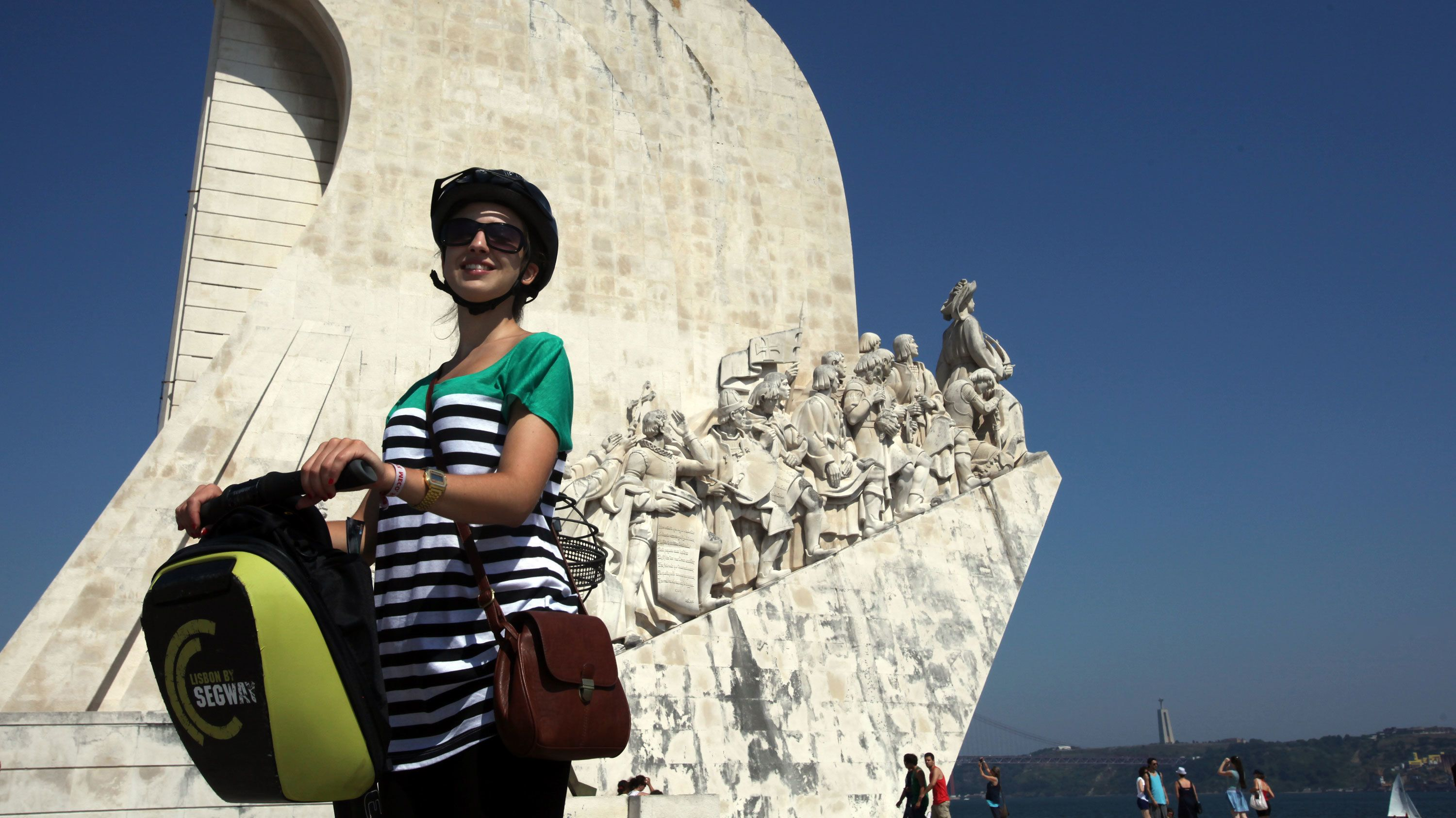 Segway riding woman in front of the Monument to the Discoveries in Lisbon