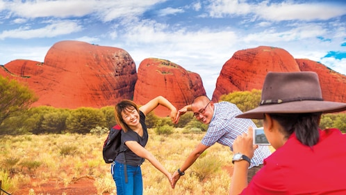 couple making heart shape with their arms at Ayers Rock in Australia