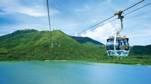 Cable car making its way over a lake to lush mountains in Hong Kong.