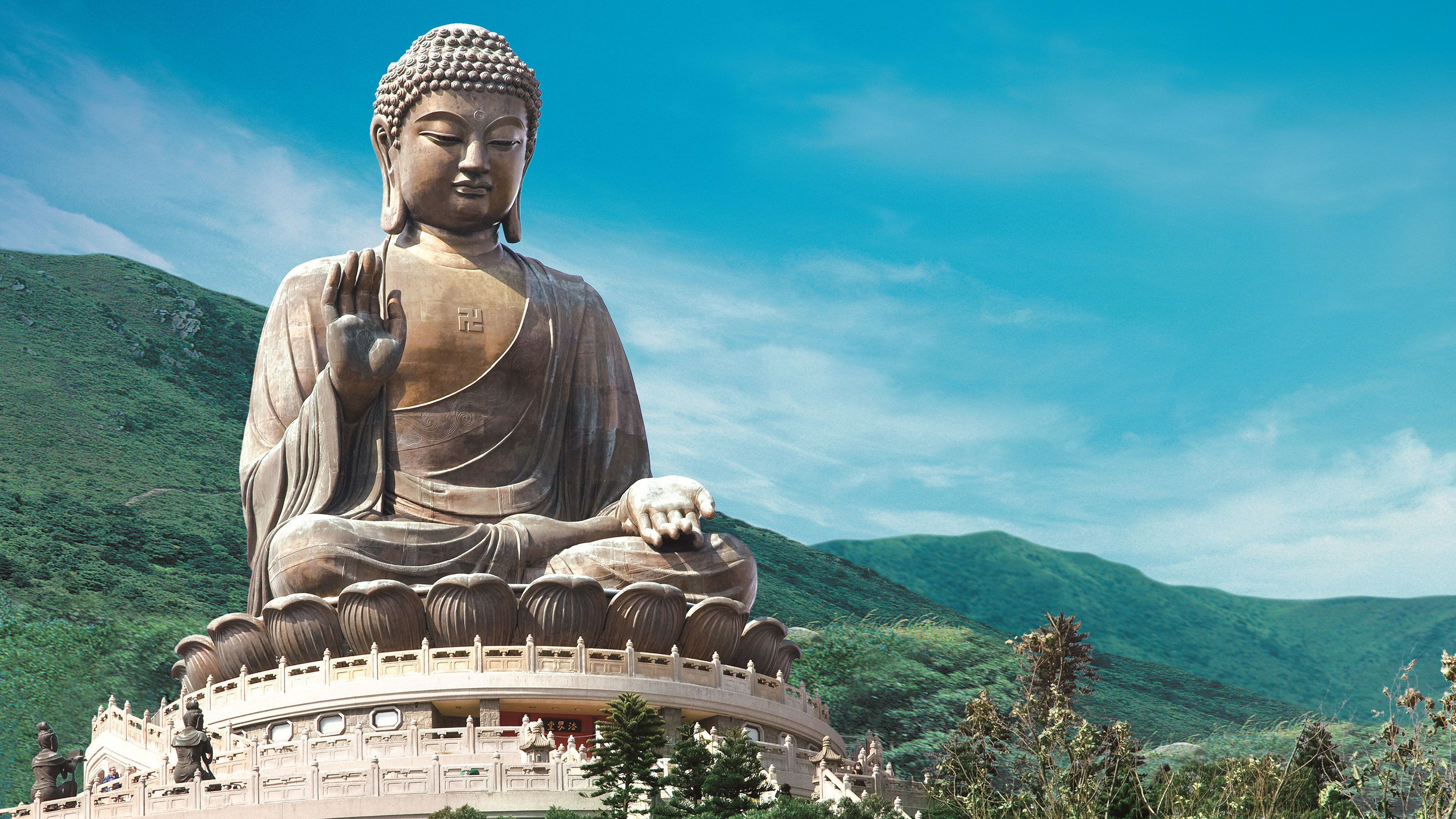 Large Buddha statue surrounded by mountains in Hong Kong.