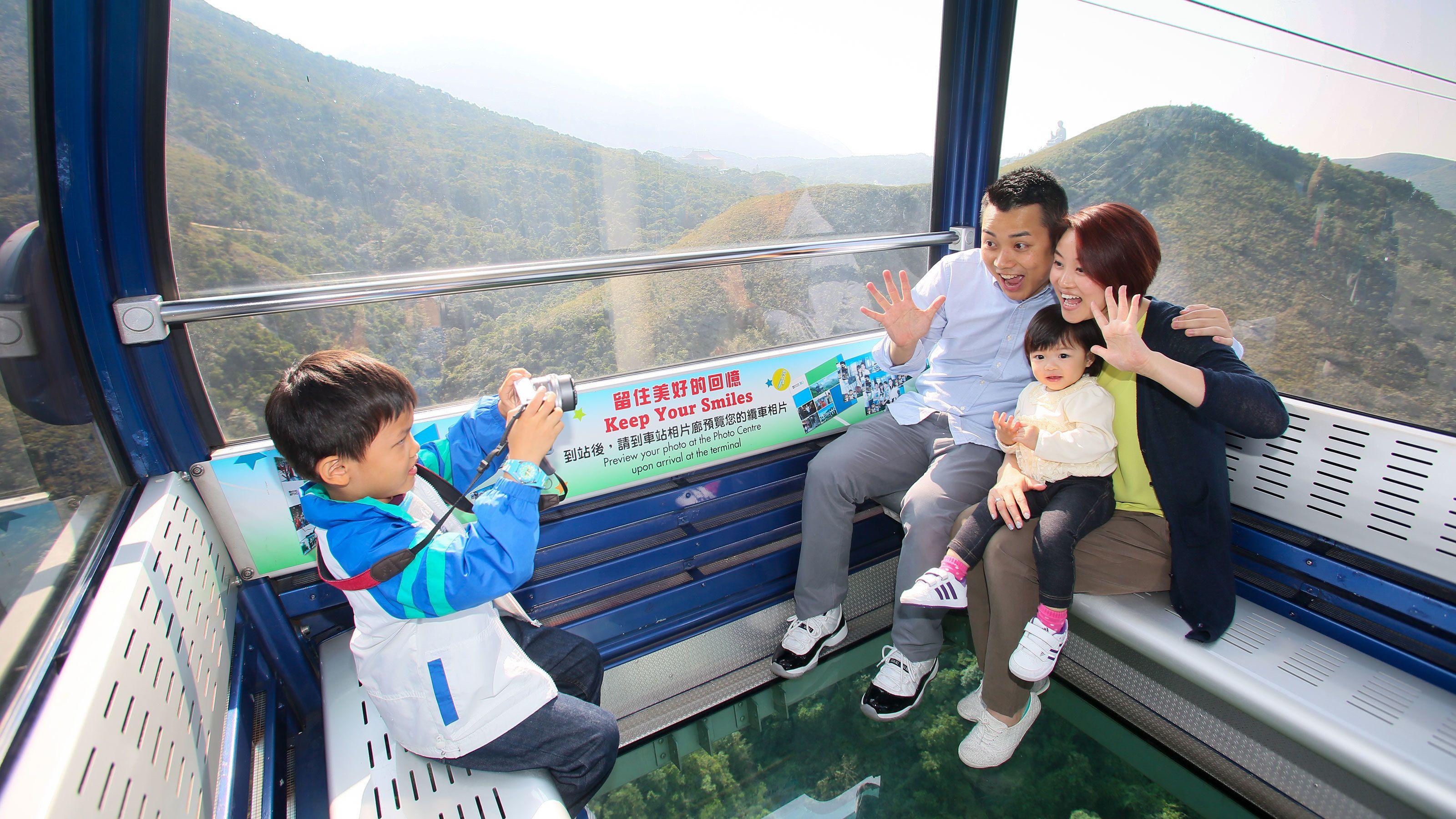 Family taking photos inside a cablecar.
