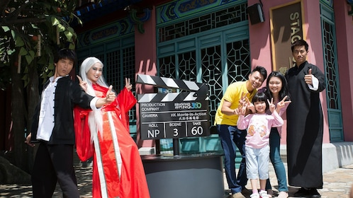 Family and performers posing for a photo in Hong Kong.