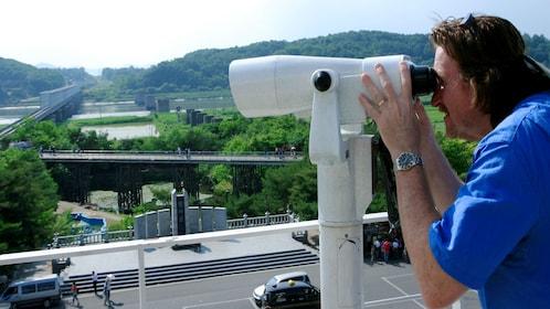 Man looking through binoculars at the DMZ in Seoul