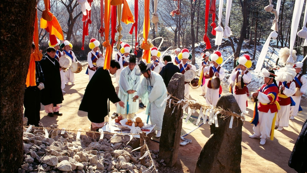 People in traditional clothes performing a traditional shamanistic rite at a Korean Folk Village