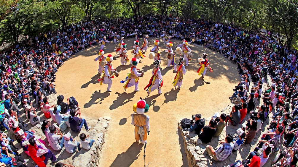People in traditional clothes performing nongak or traditional farmers music at a Korean Folk Village